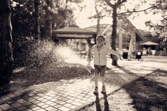 Un garçon et un pulvérisateur de l'eau Photos libres de droits