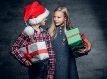 Un garçon et une fille blonde tient des boîte-cadeau Photos libres de droits