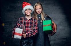 Un garçon et une fille blonde tient des boîte-cadeau Photos stock