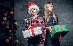 Un garçon et une fille blonde tient des boîte-cadeau Image stock