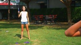 Un garçon et une fille d'adolescent jouent au badminton sur une pelouse verte dans l'arrière-cour de leur maison clips vidéos