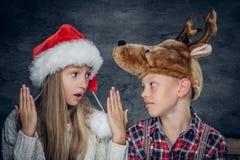 Un garçon et une fille dans des chapeaux de Noël Photographie stock libre de droits