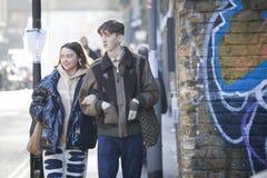 Un garçon et une fille, habillés comme hippies, vont sous la poignée sur une ruelle de brique photos libres de droits