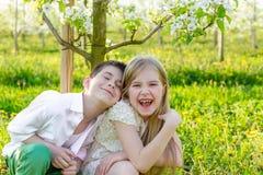 Un garçon et une fille se reposent dans un jardin de floraison au printemps Photographie stock