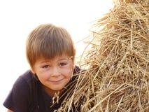 Un garçon et une pile de paille d'isolement Photo stock