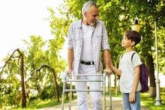 Un garçon et un vieil homme sur des échasses pour des adultes marchent en parc Photos libres de droits