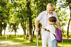 Un garçon et un vieil homme sur des béquilles marchent en parc Le garçon tient la main du ` s de vieil homme Image stock