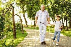 Un garçon et un vieil homme sur des béquilles marchent en parc Le garçon tient la main du ` s de vieil homme Images stock