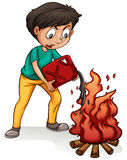 Un garçon faisant un feu de camp Image libre de droits