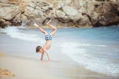 Un garçon faisant une roue dans le ressac de mer Photographie stock