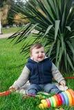 Un garçon heureux d'an en parc se reposant sur l'herbe verte Photos libres de droits