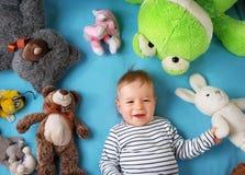 Un garçon an heureux se trouvant avec beaucoup de jouets de peluche Photographie stock libre de droits