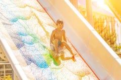 Un garçon heureux sur la glissière d'eau dans une piscine ayant l'amusement pendant des vacances d'été dans un beau parc d'aqua u photos stock