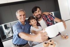 Un garçon, un homme et un vieil homme posent dans la cuisine avec les tasses de thé, qu'ils tiennent dans le leur tendu arme Photos stock