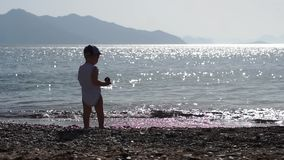 Un garçon jette un caillou dans l'eau de mer brillante du soleil, mouvement lent banque de vidéos
