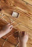 Un garçon jouant avec des allumettes Le jeune garçon joue des bâtons de match sur le fond en bois images libres de droits
