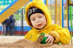 Un garçon jouant avec le sable Images libres de droits