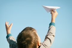 Un garçon joue avec un avion de papier de jouet contre le ciel bleu dans le domaine Photographie stock
