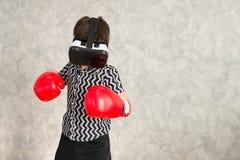 Un garçon joue le jeu de boxe avec le casque de la réalité virtuelle 3D Image stock