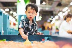 Un garçon joue le sable de la science au terrain de jeu image stock