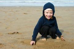 Un garçon joue sur la plage Photos stock