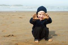 Un garçon joue sur la plage Image stock