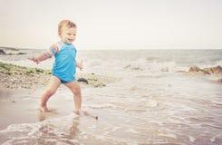 Un garçon an joue sur la plage Image libre de droits