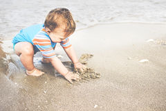 Un garçon an joue sur la plage Photographie stock