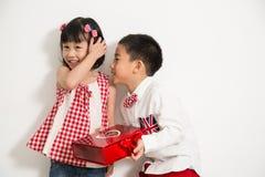 Un garçon jugeant présent pour donnent un cadeau Photos stock