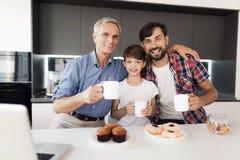 Un garçon, l'homme et un vieil homme posent dans la cuisine avec des tasses de thé Ils sourient Devant eux un ordinateur portable Photographie stock