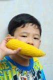 Un garçon mangeant du maïs bouilli Image libre de droits