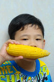 Un garçon mangeant du maïs bouilli Photographie stock libre de droits