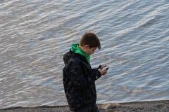 Un garçon marche autour des Iles Féroé jouant avec le smartphone photos libres de droits