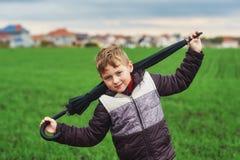 Un garçon marche un jour d'automne dans le domaine avec le parapluie Photo stock