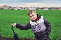 Un garçon marche un jour d'automne dans le domaine avec le parapluie Photo libre de droits