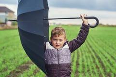 Un garçon marche un jour d'automne dans le domaine avec le parapluie Photographie stock libre de droits