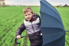 Un garçon marche un jour d'automne dans le domaine avec le parapluie Images libres de droits
