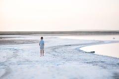 Un garçon marche le long du rivage du lac Un rivage de lac salt Salt Lake Images libres de droits