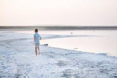 Un garçon marche le long du rivage du lac Un rivage de lac salt Salt Lake Photos stock