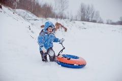 Un garçon marche sur la neige Photographie stock libre de droits