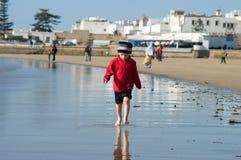 Un garçon marche sur le rivage d'océan au Maroc photographie stock libre de droits