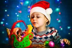 Un garçon mignon dans un chapeau Santa regarde un cadeau Noël Sleigh de sucrerie photographie stock