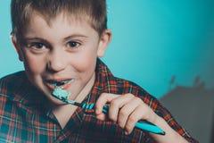 Un garçon mignon dans dents de brosses de pyjamas avec la pâte dentifrice avant heure du coucher sur un fond bleu photos stock