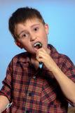 Un garçon mignon dans dents de brosses de pyjamas avec la pâte dentifrice avant heure du coucher sur un fond bleu image stock