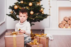 Un garçon mignon s'accroupissant à côté d'un arbre de Noël, à côté de beaucoup de cadeaux avec des rubans et des arcs d'or Type d Photographie stock
