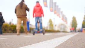 Un garçon montant un gyroboard à côté de son père Mouvement lent banque de vidéos
