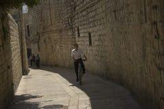 Un garçon montant une bicyclette dans la vieille ville de Jérusalem, et la Terre Sainte Images libres de droits