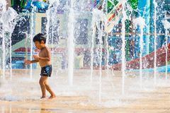 Un garçon ont plaisir à jouer avec la fontaine d'eau de plancher chez Cartoon Network photos libres de droits