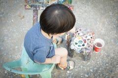 Un garçon plongeant la brosse dans la palette Photos libres de droits