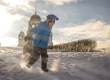 Un garçon porte son frère sur un traîneau par la neige pure images libres de droits